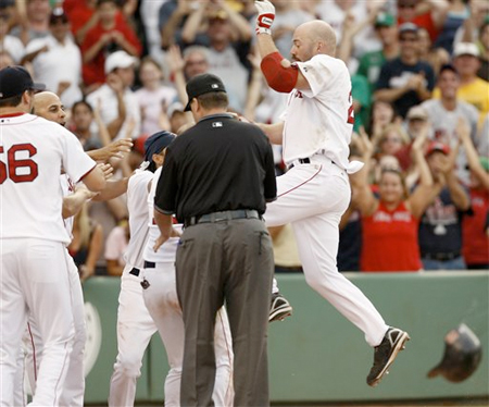 Kevin Youkilis is greeted at homeplate by his teammates